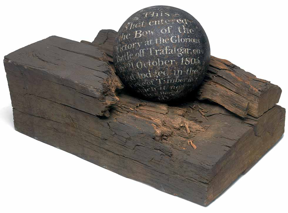 Bala de cañón de hierro en trozo de madera.