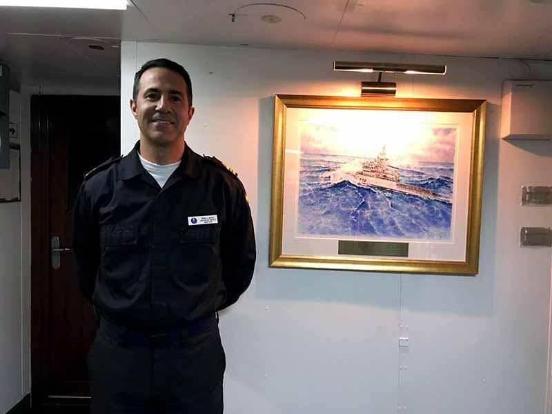 Comandante del patrullero Vigía P-73 posando con la pintura de su buque realizada por Ildefonso Palomares